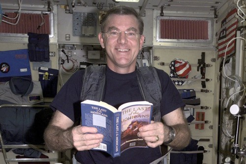 Astronaut James Voss reading in space.  (Photo: NASA via LibraryThing)